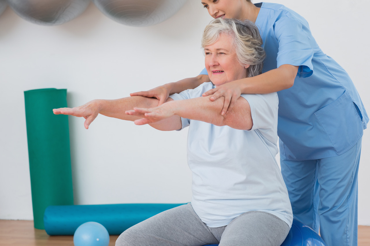Instructor assisting senior woman to exercise in gym